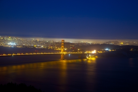 famous golden gate bridge by night with reflections in the water photo