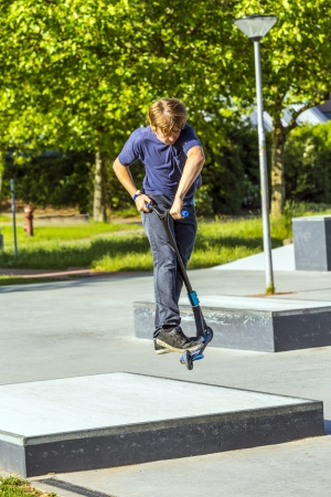 boy has fun riding his push scooter at the skatepark photo