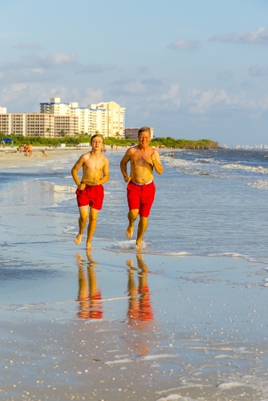 father and son enjoy jogging along the beautiful beach photo
