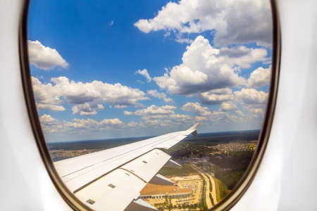 lookout of aircraft window to landscape while landing photo