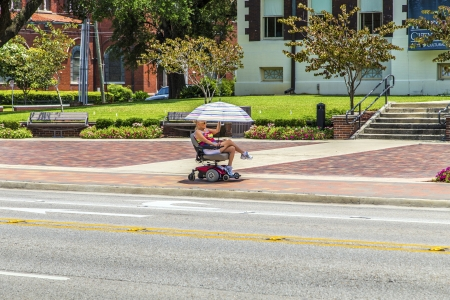 Lake Charles, USA - AUGUST 9:   attracive lady rides in her electric wheelchair on August 9, 2013 in Lake Charles, USA. Electric wheelchair was invented after WW2 by George Johann Klein for the injured war veterans.