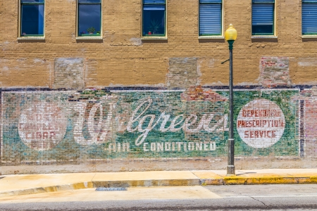 alf: Lake Charles, USA - AUGUST 9:   old painted advertising at the wall on August 9, 2013 in Lake Charles, USA. Painted ads on brick walls were common in the first alf of last century in america.