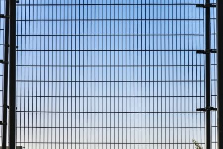 distorted image: fence with grid structure with blue sky in background Stock Photo