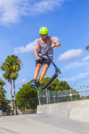 teenage boy has fun riding his push scooter at the skate park