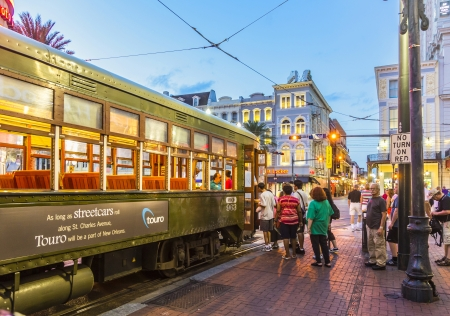 tourists stop: NEW ORLEANS - JULY 14: people travel with the famous old Street car St. Charles line on July 14, 2013 in New Orleans, USA.  It is the oldest continually operating street car line in the world.