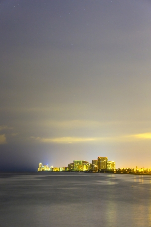 intercoastal: skyline of Miami sunny isles by night with reflections over the ocean