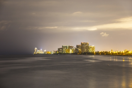 skyline of Miami sunny isles by night with reflections over the ocean photo