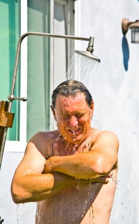 Mann hat eine Dusche im Garten