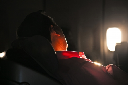 man sleeping in the seat of an aircraft in sunrise photo