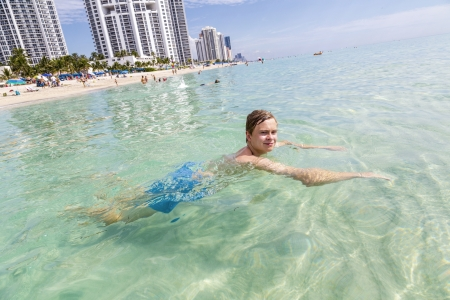 handsome teen has fun swimming in the ocean photo