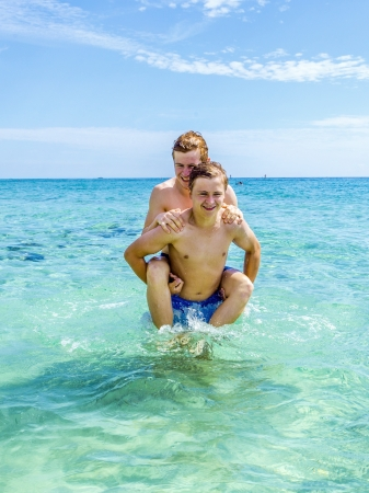 handsome teen have fun playing piggyback in the ocean photo