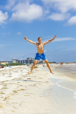 boy jumps in the air at the beach photo