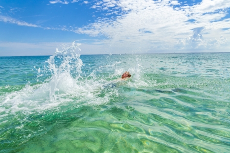 handsome teen backstroking in the clear ocean