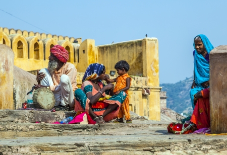 begs: JAIPUR, INDIA - OCTOBER 19  woman begs for money with her child,sitting at the entrance of AMber Fort on October 19, 2012 in Jaipur, India  Begging with children is popular at touristic spots  An old snake charmer sits beside her