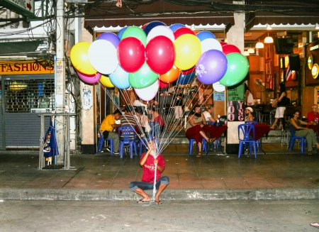 BANGKOK, THAILAND - DECEMBER 03:  Man waits for tourists in Khao San Road to sell balloons  on December 03, 2006 in Bangkok, Thailand. Situated in the area of  Banglampu, Khao San Road  is one of Bangkok's most famous streets.