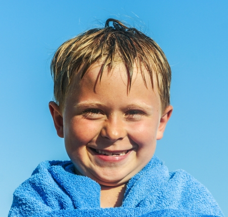 portrait of happy cute boy at the beach with towel photo