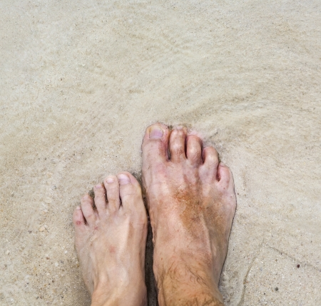 feet of father and son side by side at the beach photo
