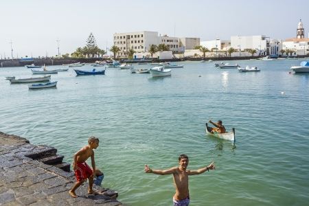 remodelled: ARRECIFE, SPAIN - AUGUST 9  boy paddles with his small canoe at the charco de San Gines on August 9, 2007 in Arrecife, Spain  The harbor area was remodelled by Canarian architect Cesar Manrique in 1984