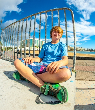 cute boy is sitting on a ramp at the skate park and smiles photo