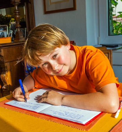 schooler: boy prepares his homework for school at the table in the living room Stock Photo