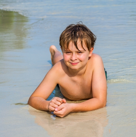 koh samet: boy is lying at the beach and enjoying the warmness of the water and looking self confident and happy