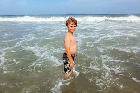 boy enjoys the beautiful beach in windy weather photo