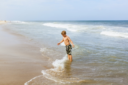 outerbanks: boy has fun standing in the ocean in the stormy beach