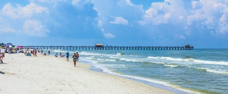 NAPLES, USA - JULY 27: people enjoy the beautiful public white beach at Naples Pier on July 27, 2013 in Naples, USA. The beach is lively and is lined with some of Naples most luxurious homes, many visible from atop the pier