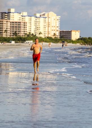 man enjoys jogging along the beautiful beach photo