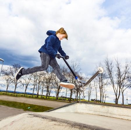 jongen gaat airborne meteenbetrouwbaarheid scooter Stockfoto