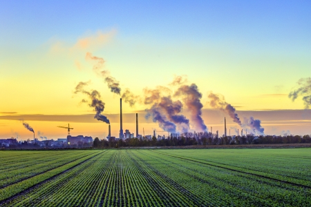 industry complex in Frankfurt in early morning with green fields and smoking chimney