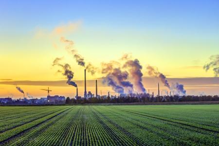 industrie complex in Frankfurt in de vroege ochtend met groene velden en rokende schoorsteen Stockfoto