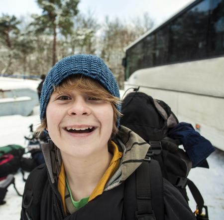 teenager with backpack on a winter trip in snow photo