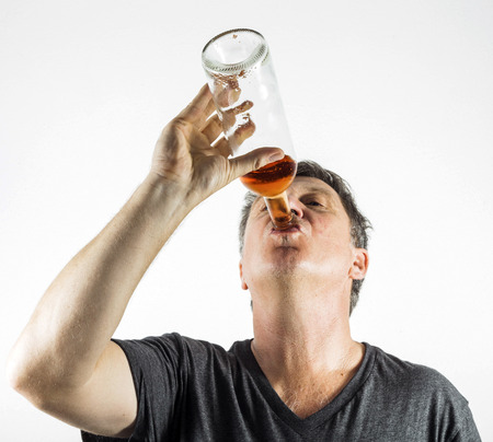 drinking alcohol: man drinking alcohol out of a bottle Stock Photo