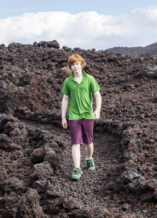 boy walking on volcanic stones in natural parc in lanzarote Stock Photo - 24391356