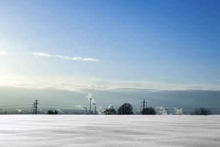 snow covered field and smoking chimneys at the horizon photo
