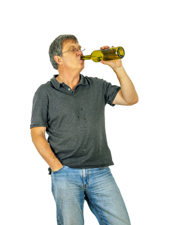 mature man drinks alcohol out of a bottle