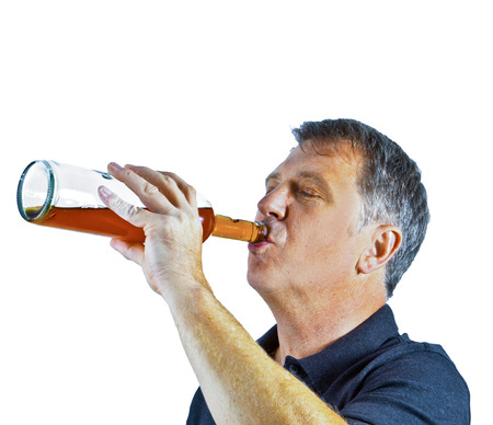 drinking alcohol: man drinking alcohol out of the bottle Stock Photo