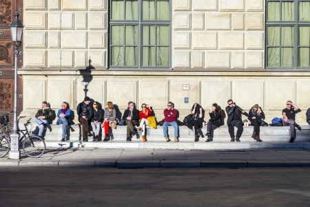 residenz: MUNICH, GERMANY - DEC 27: people wait in the sun in front of residence on  Dec 7, 2013 in Munich, Germany.  The Residenz is the largest city palace in Germany and   open to visitors.