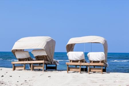 Strandligstoel voor koppels op het strand met blauwe hemel en uitzicht op de oceaan