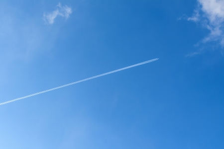 blue sky with condensation trail of aircraft photo