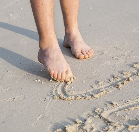 adult footprint: feet of a boy is painting figures in the fine sand of the beautiful beach
