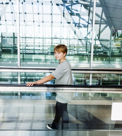 boy in the departure hall on a moving staircase photo