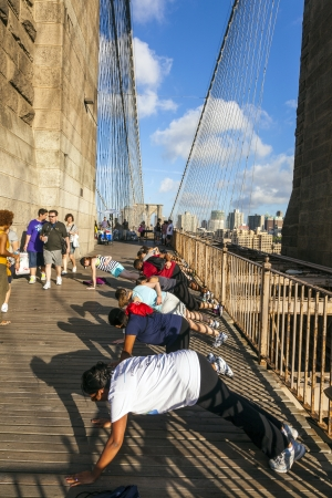 NEW York, USA - July 7: people exercise push-up at Brooklyn bridge in late afternoon on July 7,2010, New York. Brooklyn Bridge was constructed under Roeblings 1840 patent for the in-situ spinning of wire rope.