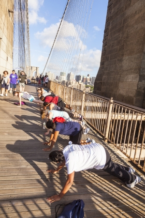 NEW York, USA - July 7: people exercise push-up at Brooklyn bridge in late afternoon on July 7,2010, New York. Brooklyn Bridge was constructed under Roebling's 1840 patent for the in-situ spinning of wire rope.