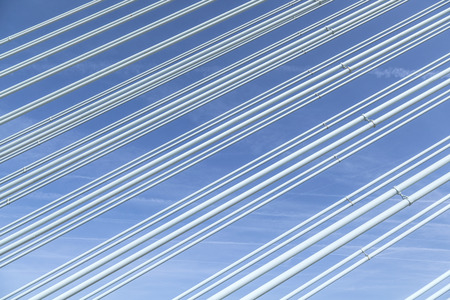 repetitious: big guyed bridge shrouds background over sky