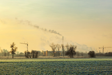 aerea: sunrise in rural aerea in wintertime with smoking chimneys at the horizon