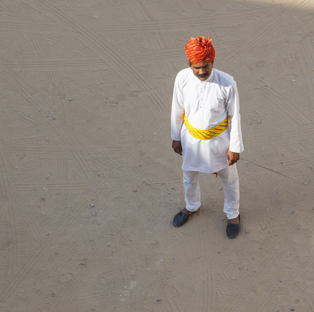 MANDAWA, INDIA - OCT 25: A Rajasthani waiter wearing traditional colorful turban passes the empty parking lot at the desert hotel on OCT 25, 2012 in Pushkar, Rajasthan, India.