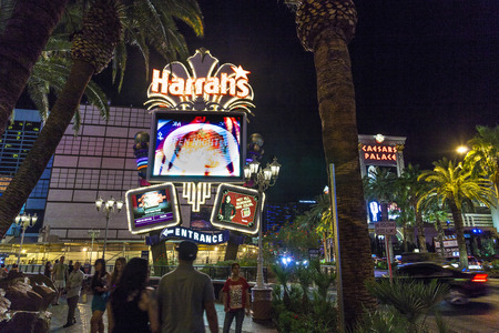renamed: LAS VEGAS - JUNE 15: people at Harrah`s neon sign on June 15, 2012. Opened in 1973 as the Holiday Casino, the property was renamed Harrahs in 1992.