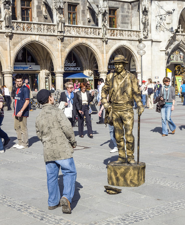 earns: MUNICH, GERMANY -APRIL 7: street pantomime at the marienplatz in Munich earns money as a typical bavarian rural old person on April 7, 2009 in Munich , Germany. Editorial